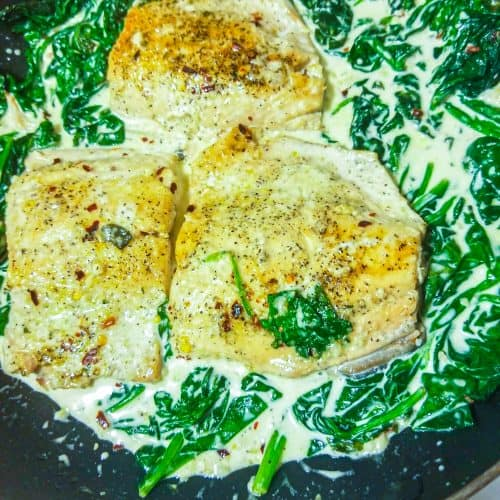 salmon with spinach cream sauce in a pan